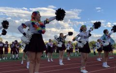 """Varsity captains, Olivia Enright, Bridget Hauger, and Lanie Kilpatrick, lead their team in their """"Hey Raptors Go SC"""" cheer. This was taken at one of the first home football games at Longmont High School of the season."""
